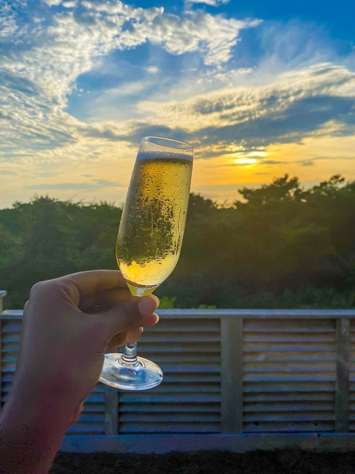 toasting flute of champagne at sunset