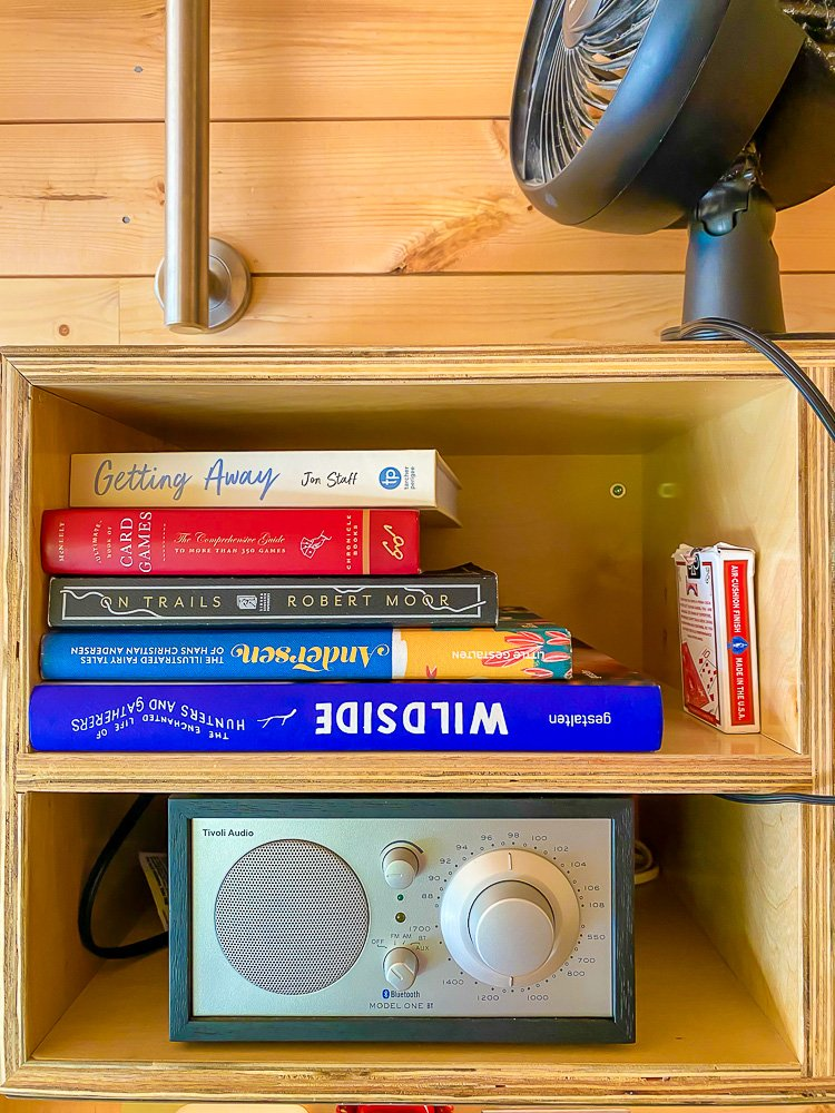 books, games, and radio on shelf in Getaway cabin