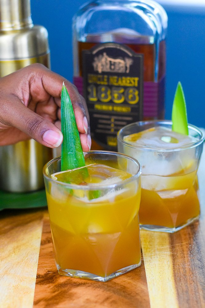 adding pineapple frond to glass to garnish whiskey cocktail