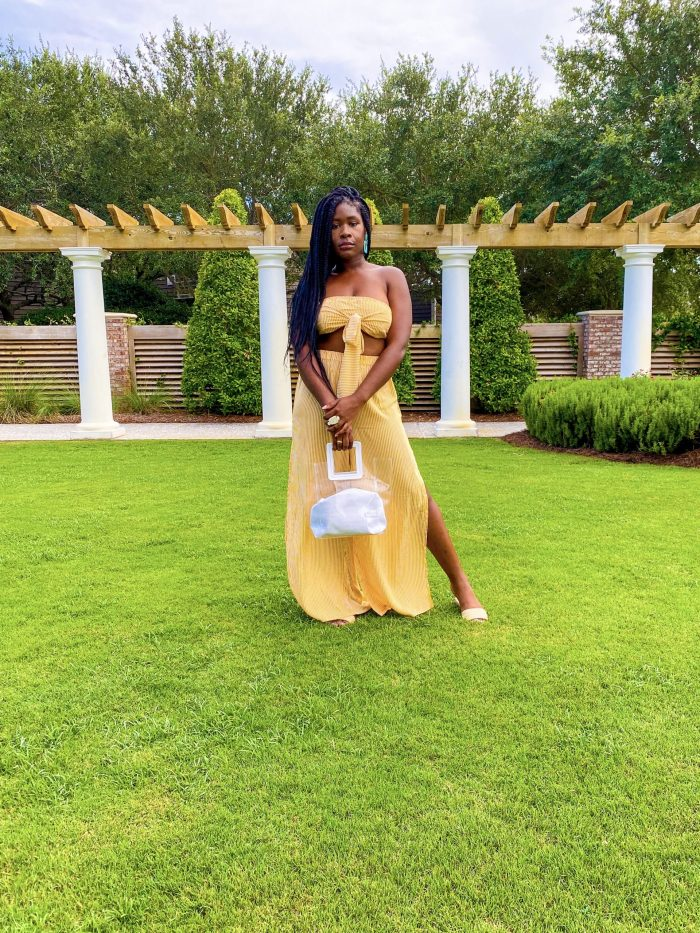 Jazzmine wearing yellow co-ord set in resort courtyard