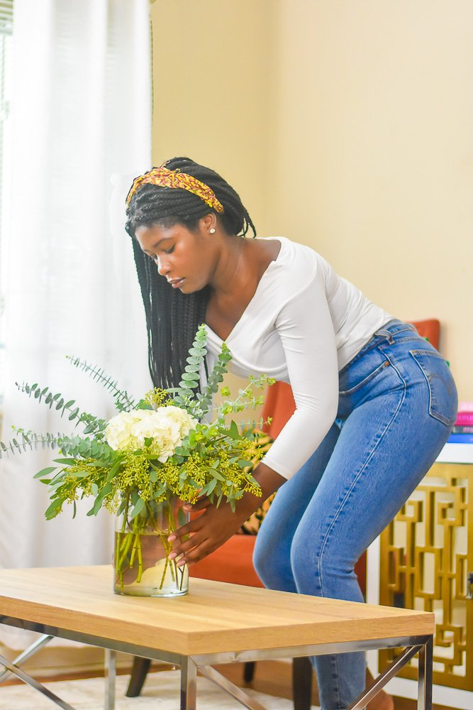 Jazzmine placing floral arrangement on coffee table
