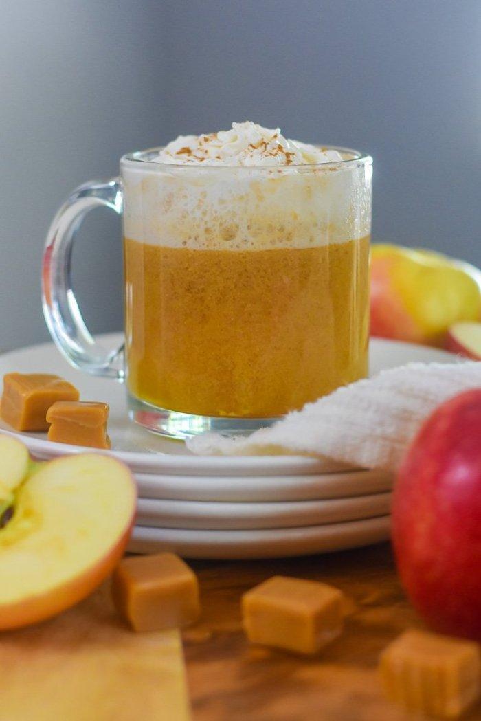mug of hot bourbon caramel apple cider on stack of saucers