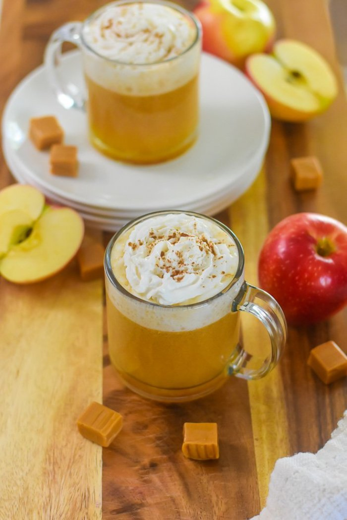 mug of bourbon caramel apple cider surrounded by apples and caramel candy