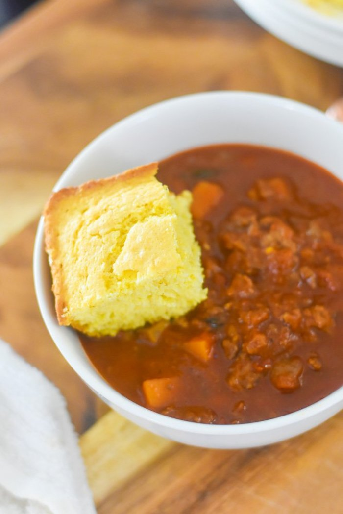 piece of cornbread on top of bowl of Moroccan-spiced chli