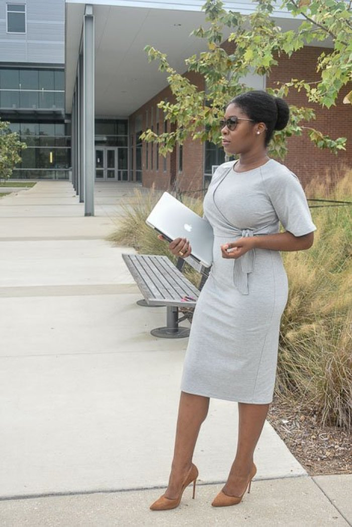 Jazzmine standing outdoors holding laptop, wearing a gray business casual sheath dress, natural hair slicked back into a bun.