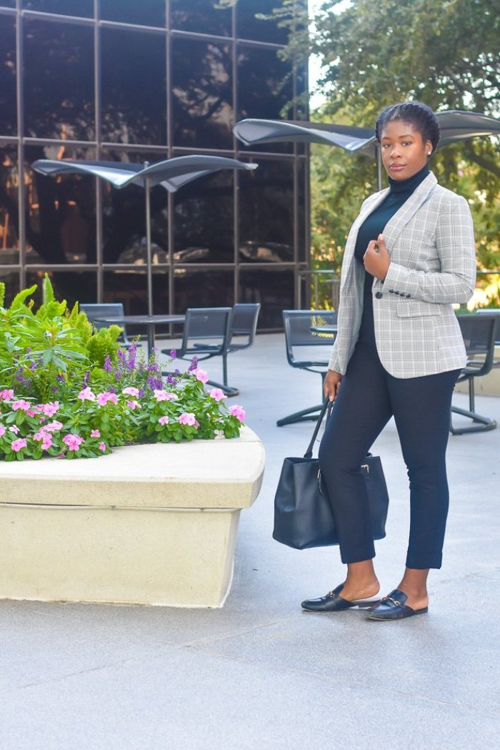 Jazzmine standing outdoors holding black handbag, wearing plaid blazer.