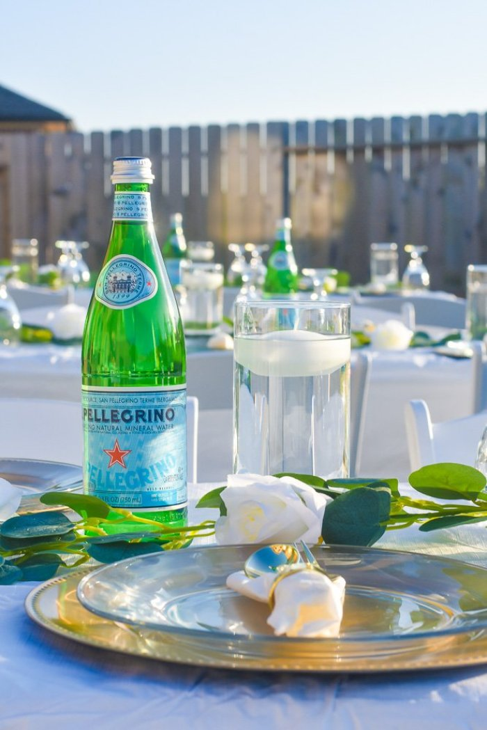 backyard tablescape with floating candles and bottles of sparkling water