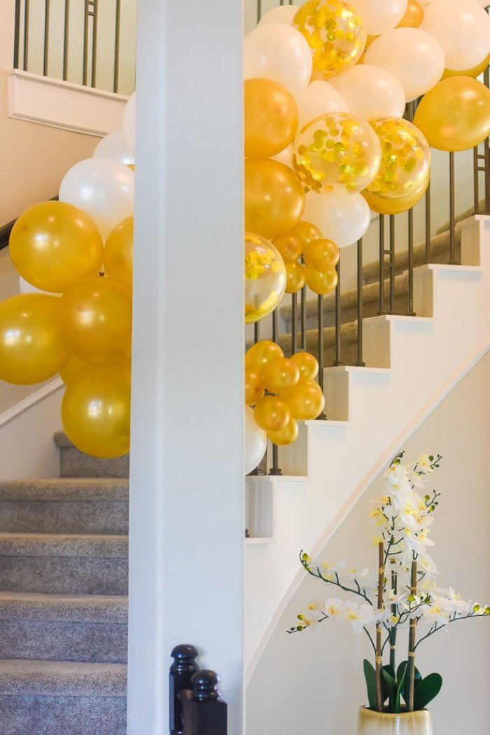 gold and white balloon garland on staircase