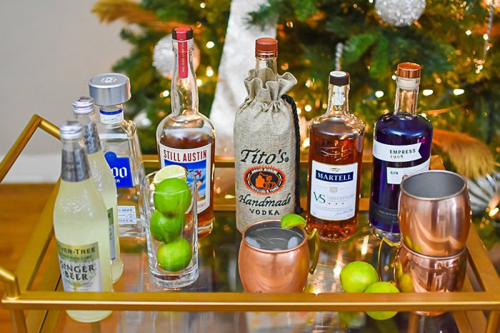 assorted liquors and ingredients for mule cocktails on top of bar cart
