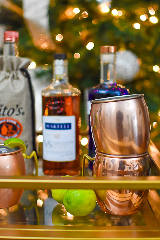 copper mugs and assorted liquors displayed on bar cart