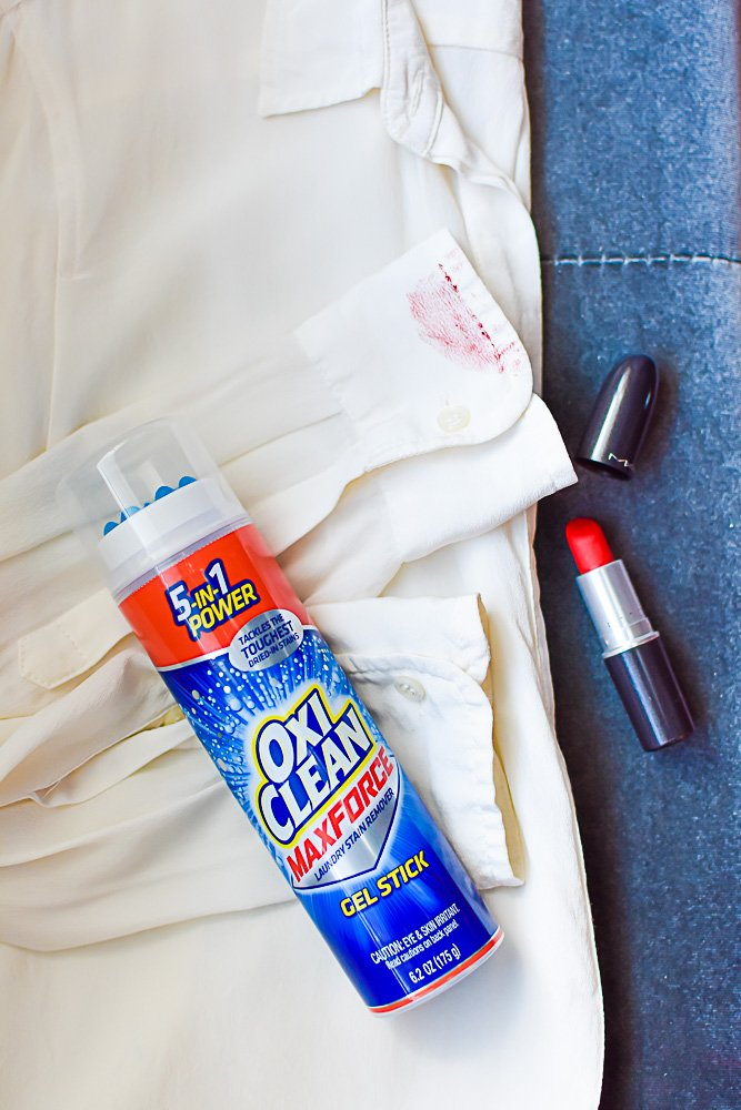 flat lay of stained white shirt, tube of red lipstick, and OxiClean gel stick