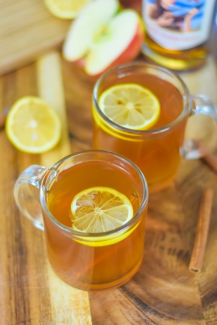 two spiced apple cider hot toddies in mugs