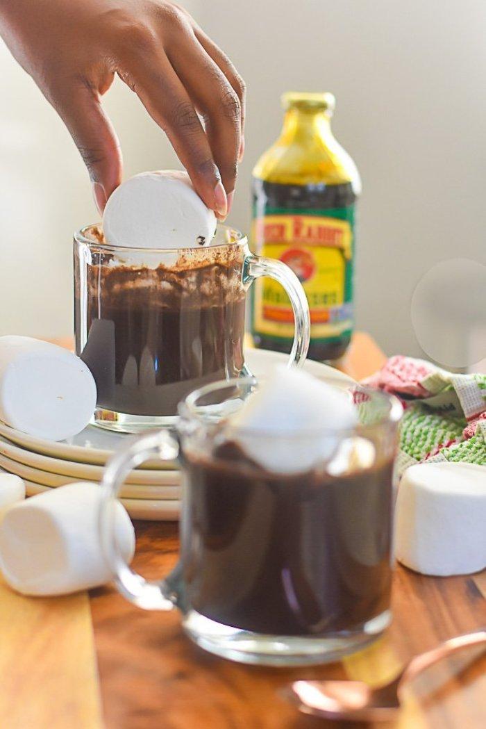 placing jumbo marshmallow in mug of bourbon gingerbread hot cocoa