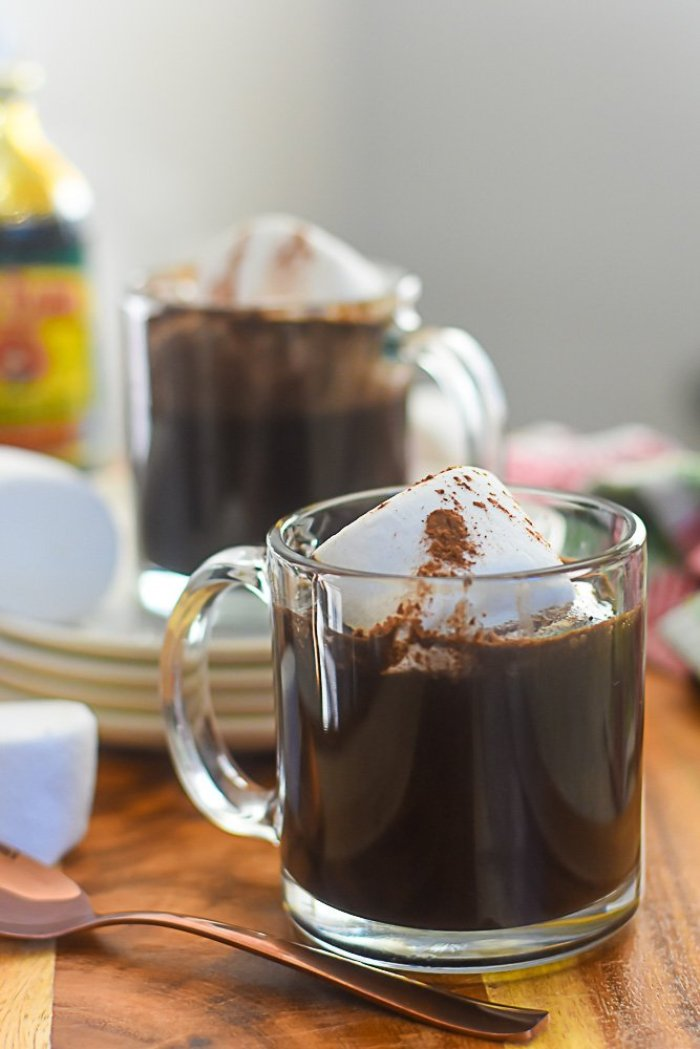 two mugs of bourbon gingerbread hot cocoa surrounded by jumbo marshmallows