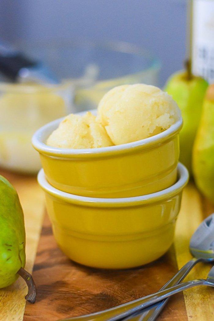 two scoops of honey riesling pear sorbet in yellow ramekin on wood cutting board