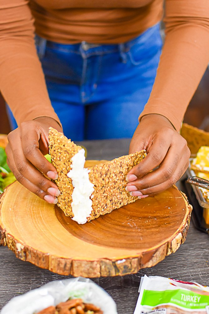 hands securing two pieces of crispbread together with cream cheese