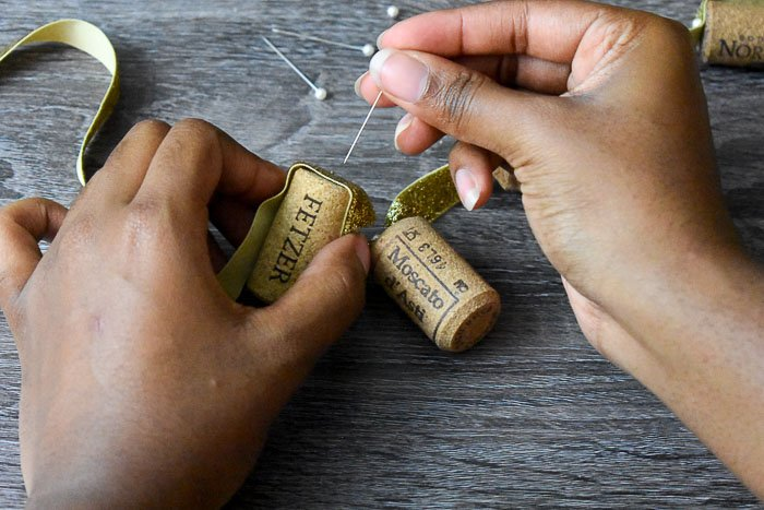 placing stick pin into ribbon and wine cork