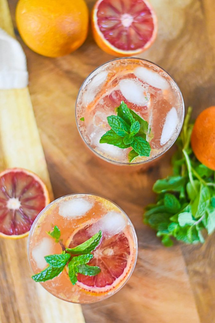 overhead view of two bourbon cocktails in rocks glasses with fresh mint and blood orange garnishes