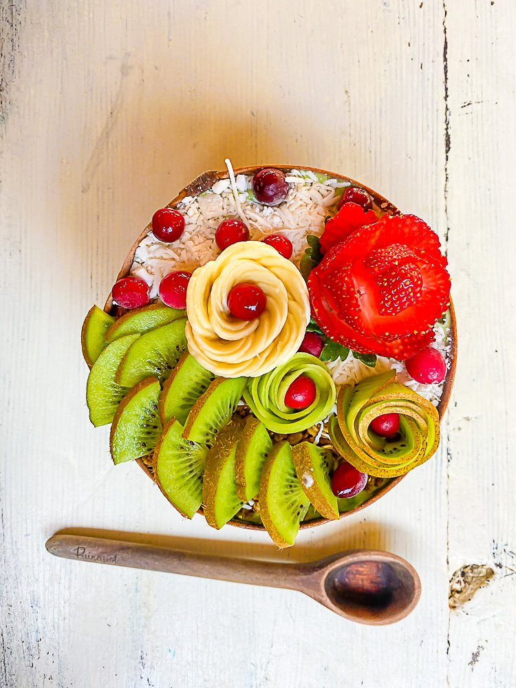 Grin smoothie bowl from adorned with fresh kiwi, banana slices, and berries arranged into flower shapes