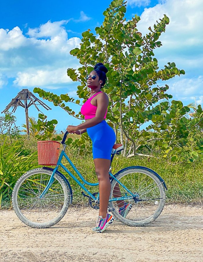 Jazzmine riding bike on Holbox Island wearing neon outfit