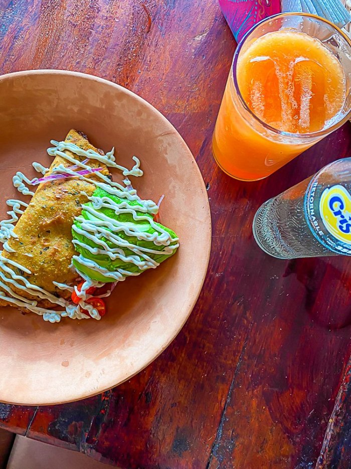 fried empanada and fresh avocado on terra cotta plate next to glass of fresh papaya juice