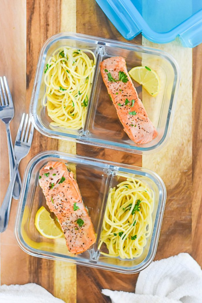 portions of seared salmon and pasta with parsley in divided glass meal prep containers