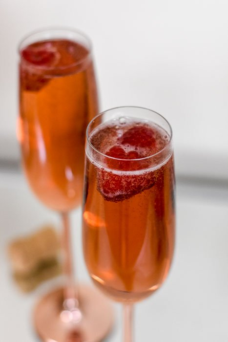 two champagne flutes with rose-colored cocktail and raspberries inside.
