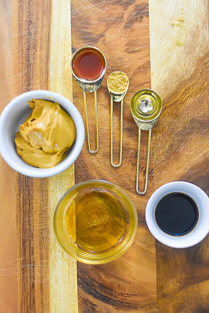 ingredients for sticky spicy peanut butter wing sauce laid out on wooden cutting board in measuring bowls and spoons