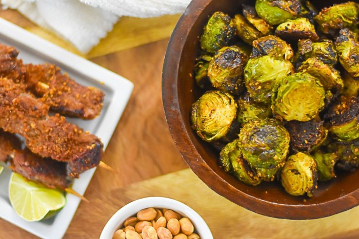 roasted brussels sprouts in wooden bowl next to plate of beef suya skewers.