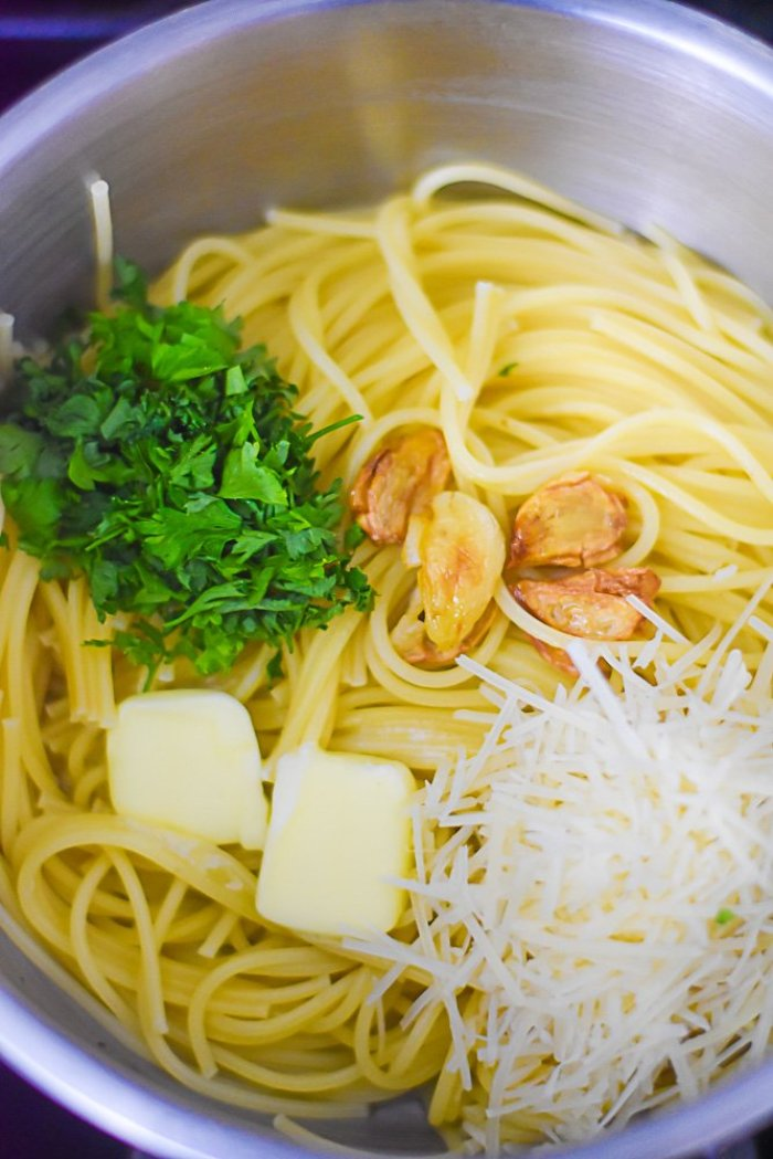 naked pasta with shredded parmesan cheese, salted butter, sauteed garlic cloves, and fresh parsley in a pot