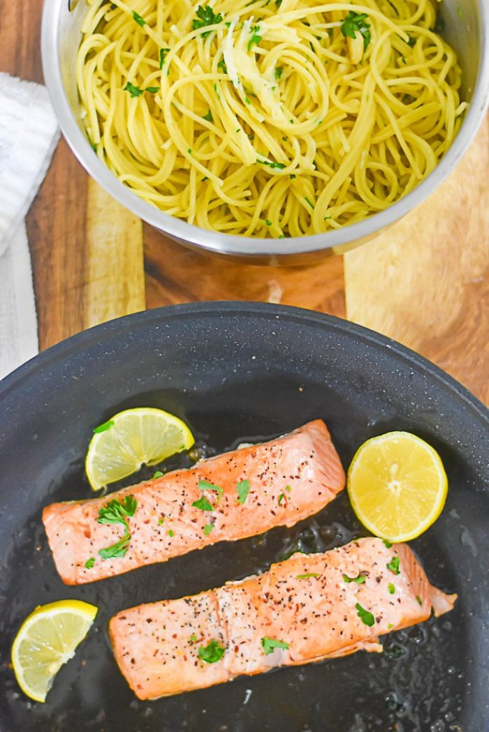 seared salmon in pan with lemon wedges next to pot of angel hair pasta