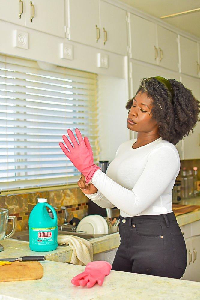 Jazzmine putting on pink rubber glove in kitchen.