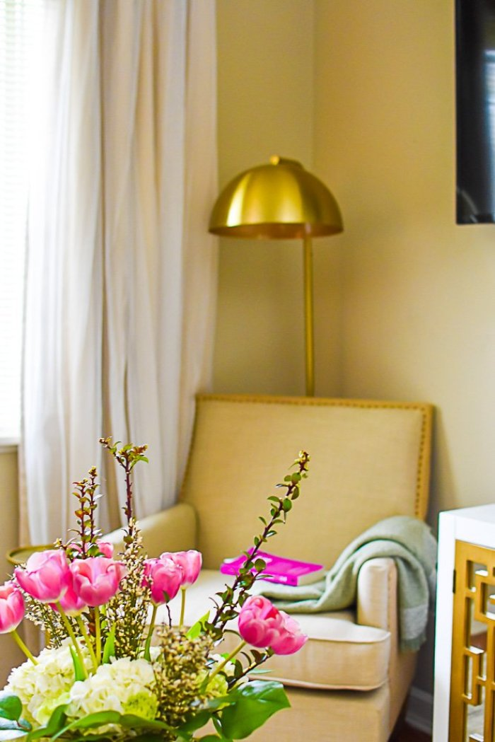 reading corner in living room in background with arrangement of tulips, and hydrangeas in the foreground.