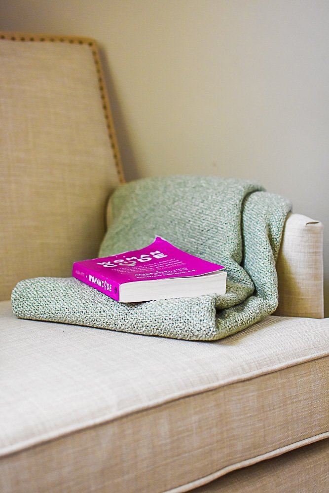 green throw blanket and pink paperback book on seat of reading chair.