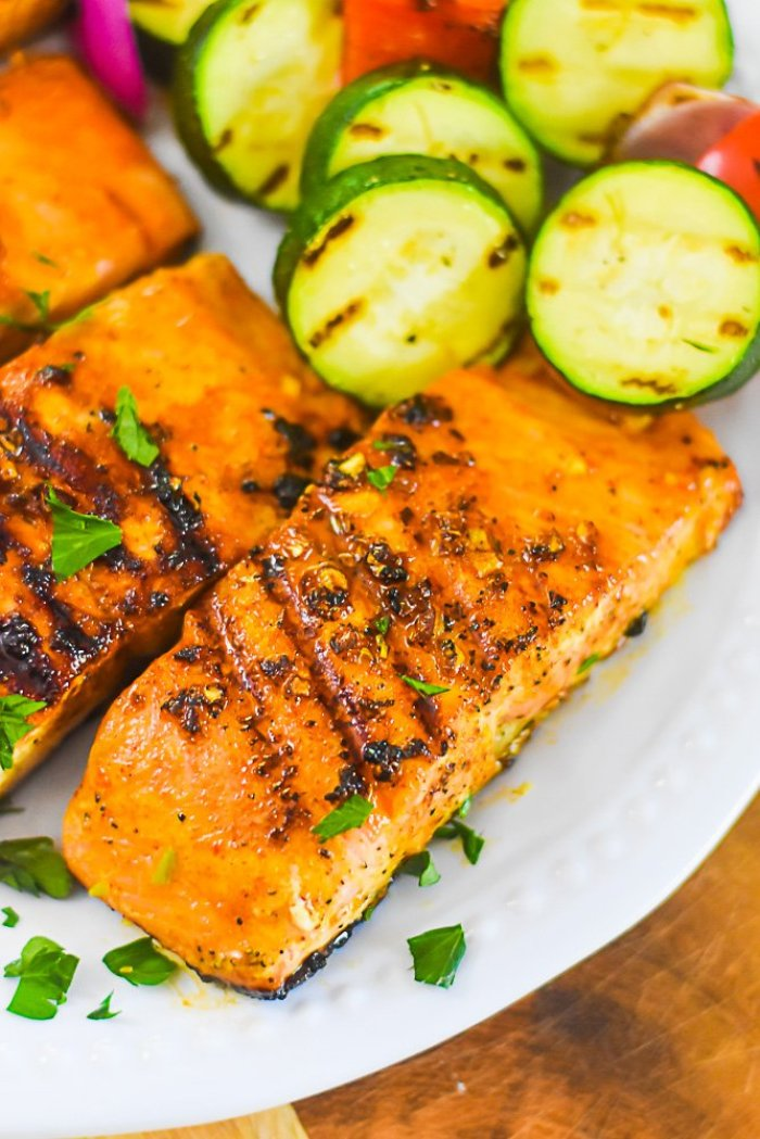 plate of grilled salmon filets with grilled zucchini and red pepper.