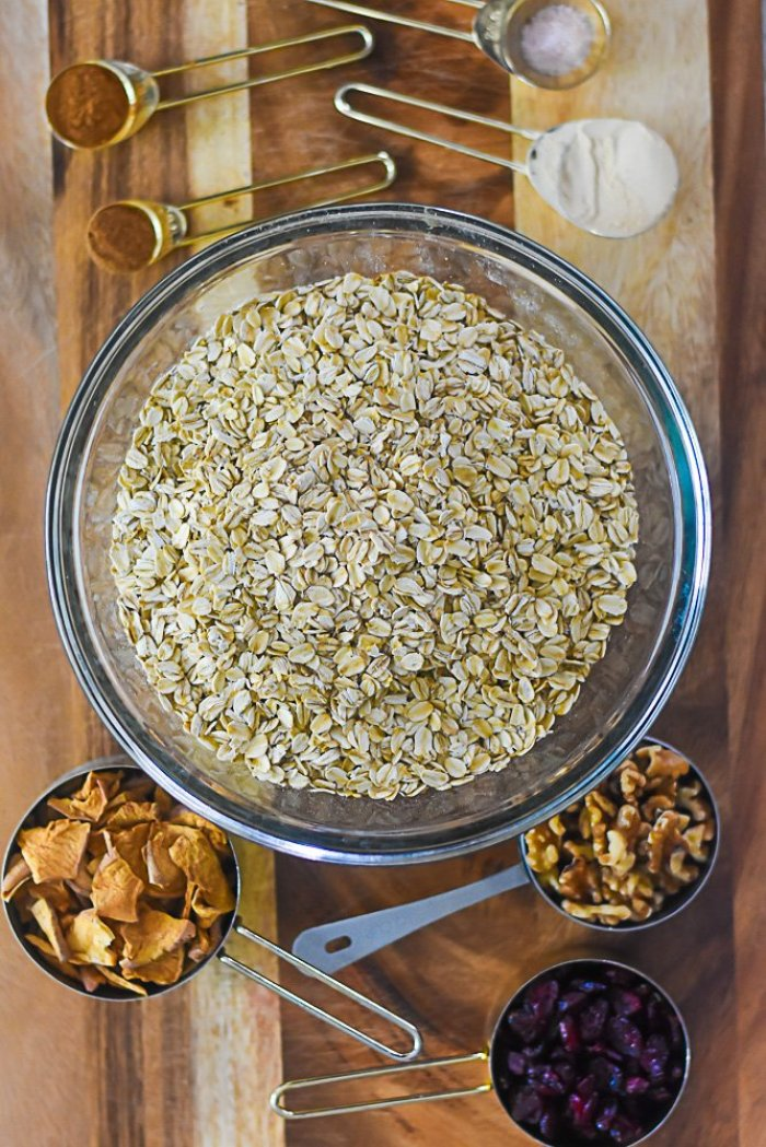 rolled oats in large bowl, surrounded by measuring cups and spoons filled with spices, fruits, and nuts.