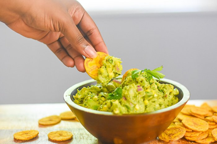 dipping plantain chip into bowl of grilled sweet corn guacamole.