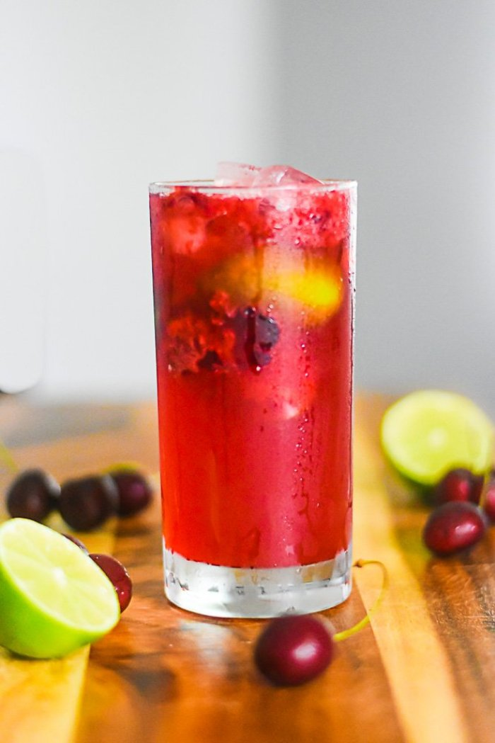 glass of cherry limeade spiked with bourbon.
