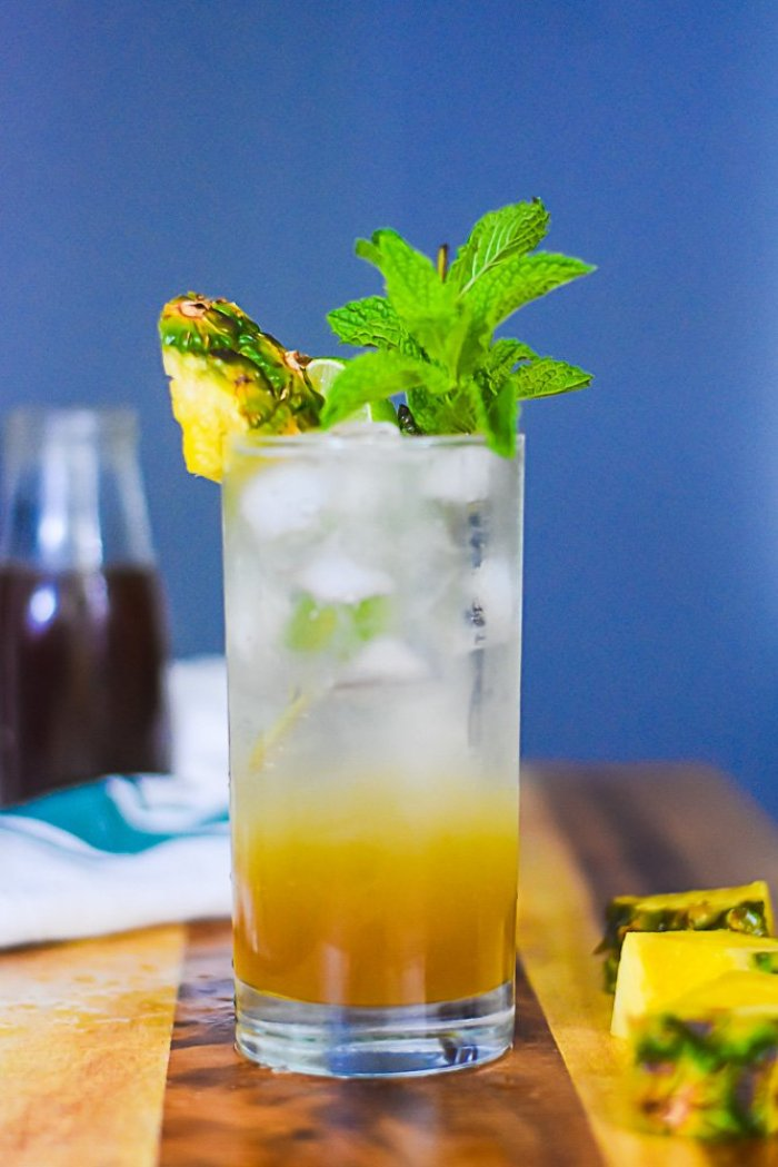 brown sugar mojito in glass next to chunks of fresh pineapple and bottle of brown sugar pineapple syrup.