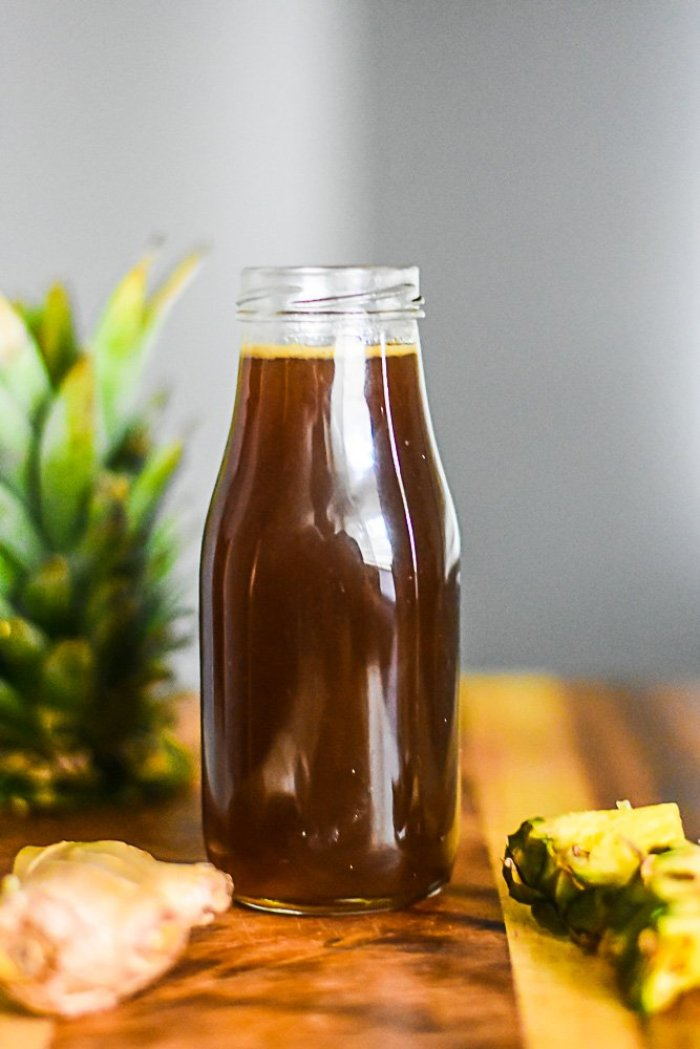 glass bottle of homemade brown sugar simple syrup infused with pineapple and ginger.