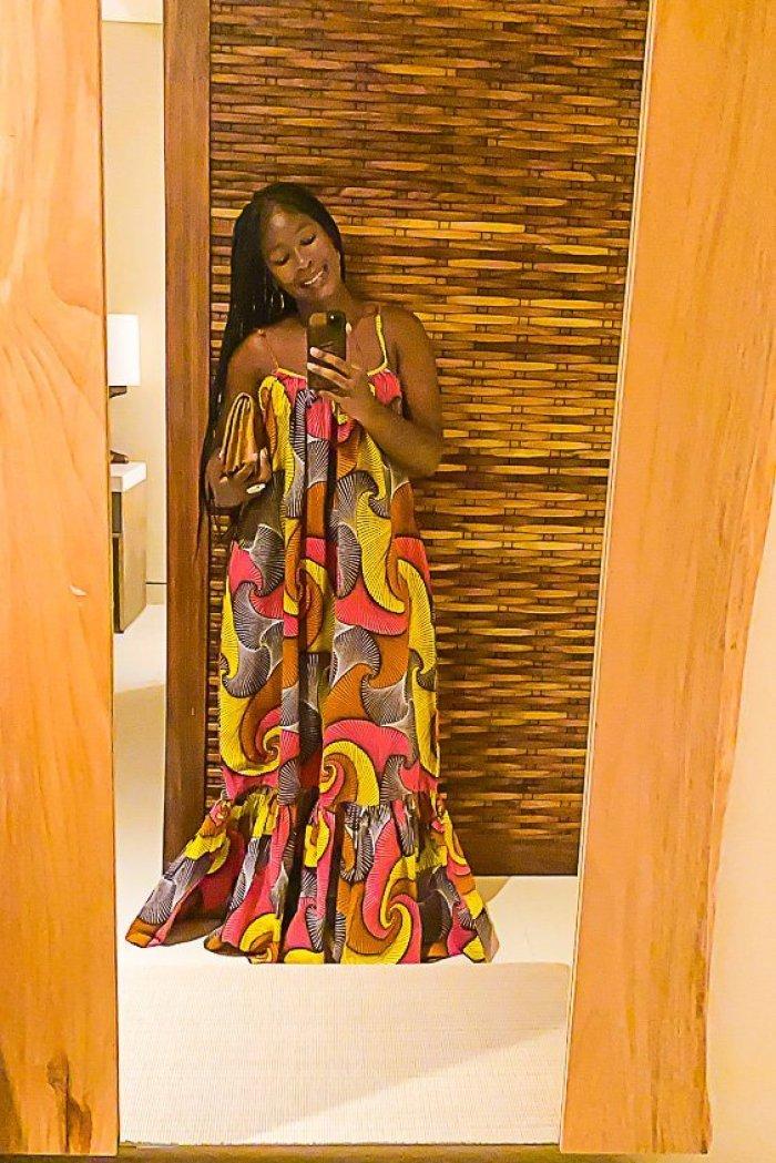 Jazzmine wearing colorful African-print maxi dress taking mirror selfie.