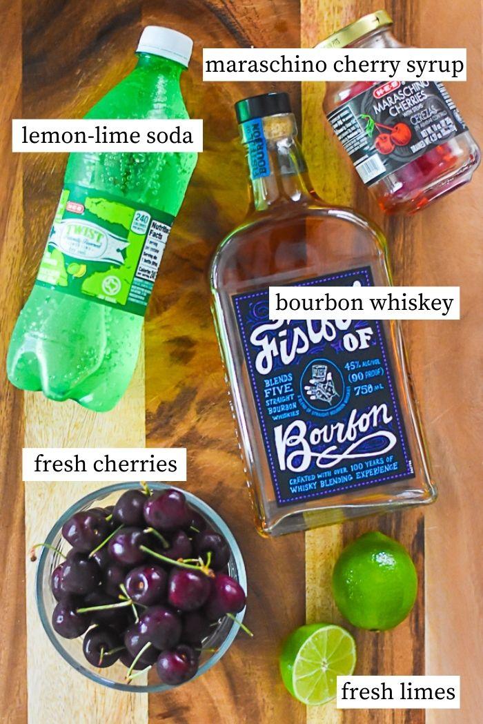 flat lay of ingredients for bourbon cherry limeade: bowl of fresh cherries, fresh limes, bottle of bourbon, bottle of lemon lime soda, jar of maraschino cherry syrup.
