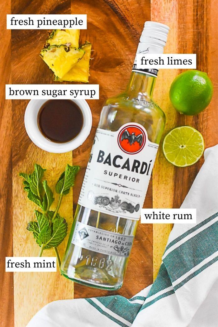 flat lay of brown sugar pineapple mojito ingredients: bottle of Bacardi white rum, fresh mint sprigs, fresh limes, small ramekin of brown sugar syrup, fresh pineapple.
