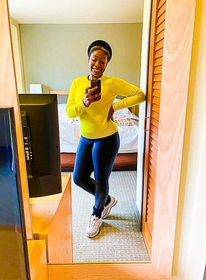 Jazzmine taking selfie in hotel mirror wearing neon green sweater and black leggings.