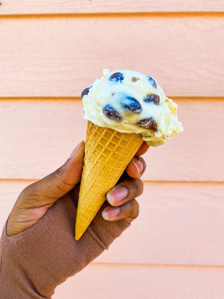holding cone of rum raisin ice cream against pink wall.