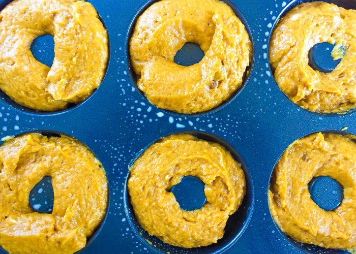pumpkin cake batter piped into a donut pan.