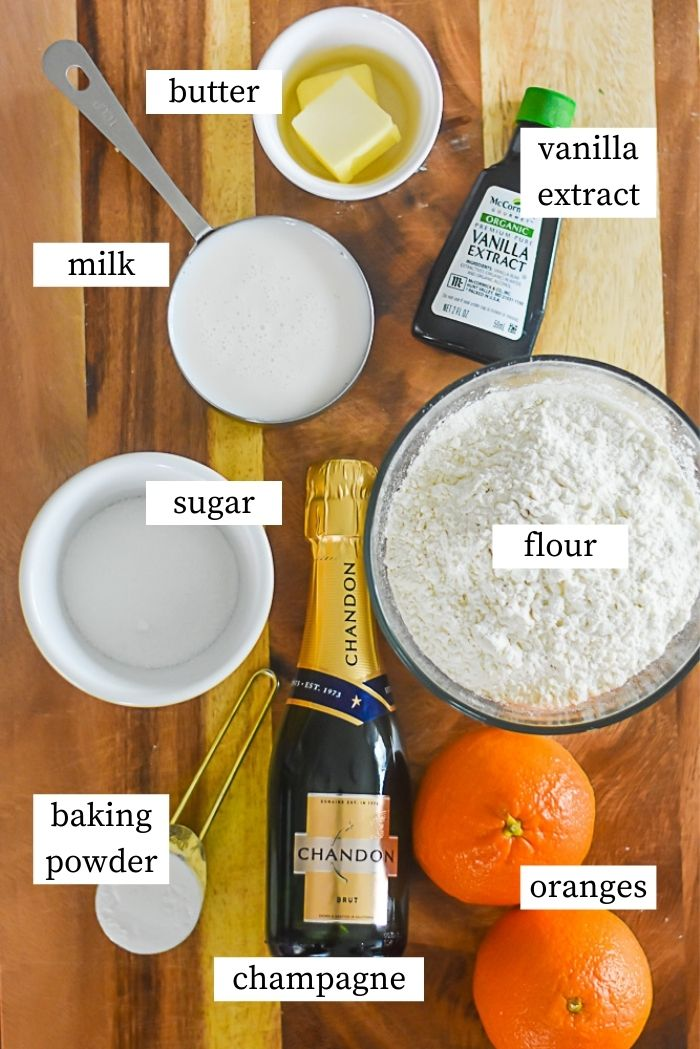 flat lay of ingredients for mimosa pancakes: two oranges, mini bottle of champagne, spoonful of baking powder, bowl of flour, ramekin of sugar, bottle of vanilla extract, two pats of butter, and measuring cup of milk on countertop.