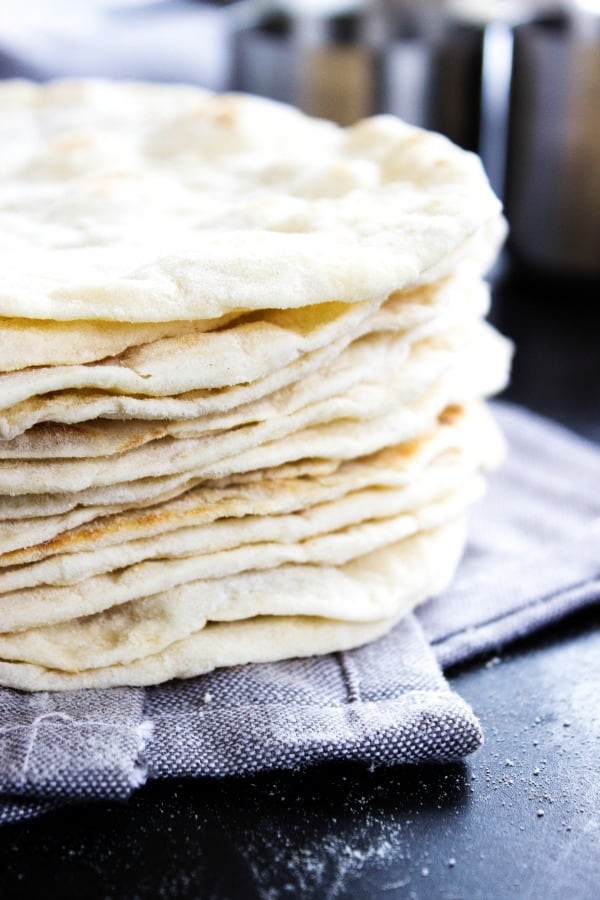 Best Ever Flour Tortillas are so easy & delicious that once you make these you'll never go back to store bought tortillas again.- stacked tortillas on grey napkin on wooden table