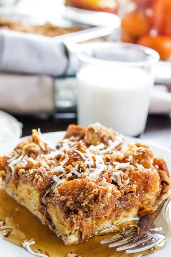 Overnight Coconut Cinnamon Pecan French Toast Casserole - Elevate your morning breakfast with this deliciously easy, make-ahead-breakfast casserole.- White plate, metal fork, glass of milk, grey napkins