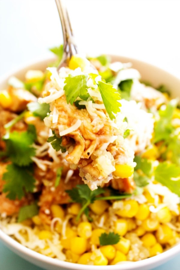 BAKED BARBECUE CHICKEN & QUINOA BOWLS - White bowl, metal fork, blue table